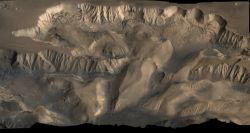 This oblique image looking north over central Valles Marineris shows Ophir Chasma (top) and Candor Chasma (lower). The connected rift valleys and basins within Valles Marineris likely formed from a combination of tectonic faulting, groundwater escape, and erosional collapse. (NASA/JPL-Caltech/US Geological Survey)