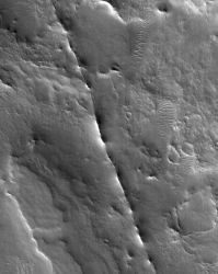 The thin ridge running down the center of the image is a volcanic dike. These occur where molten rock is forced into a fault or fracture, where it cools and hardens. If the volcanic rock is tougher than the surrounding rock (as here), erosion leaves the dike standing as a ridge. (NASA/JPL-Caltech/Malin Space Science Systems)